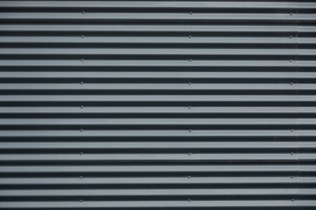Front view of grey corrugated metallic wall