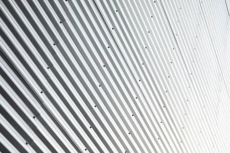 Diagonal view of building with corrugated metal wall in sunlight Stok Fotoğraf