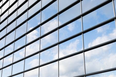Diagonal view of glass panels wall, reflecting clear sky, of modern skyscraper in Minsk city, Belarus