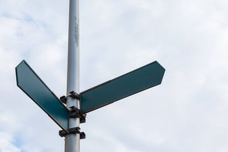 Street roadsign pointer with two arrows against a blue sky mock-up
