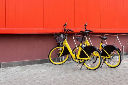 Bike renting parking at red wall, urban transport system