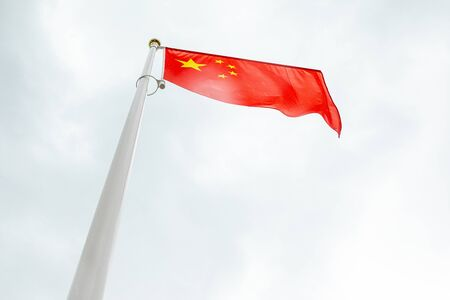 Bottom view of flag of China on a flagstuff in front of the sky
