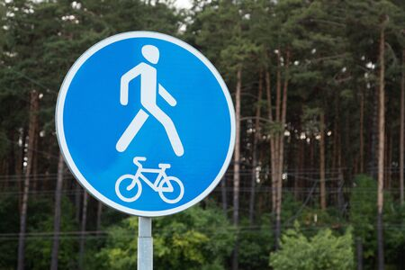 Roadsign Pedestrian and bike rider traffic allowed against forest. Photo with depth of field