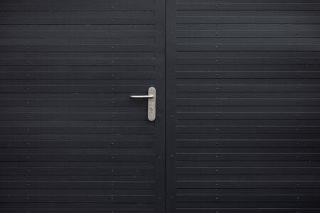 Close-up of black metal door with grey handle Foto de archivo - 129198335