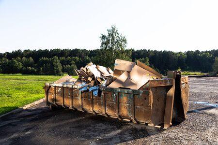 Big garbage toter full with carton against forest Stok Fotoğraf
