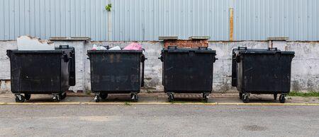Black waste bins on street, environmental pollution