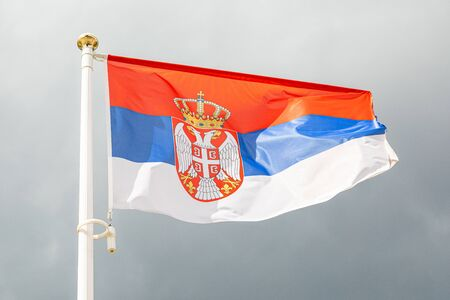 Serbian flag on a flagstuff in front of the sky