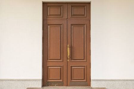 Old brown wooden doubled-up door in white wall