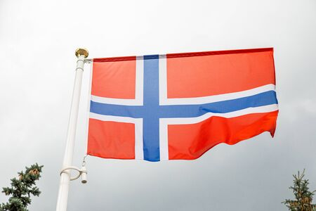 Norwegian flag on a flagstuff in front of the sky