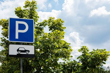 Parking roadsign in front of sky and trees 写真素材