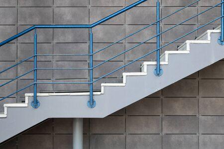 Weiße Zementtreppe mit blauem Stahlgeländer auf grau gefliestem Wandhintergrund.