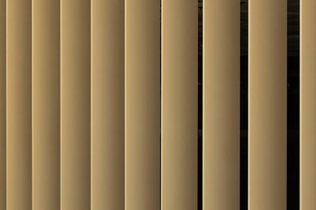 Beige or golden 3d stripes on black background. Louvre shutters like pattern