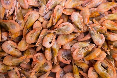 Frozen shrimps in one huge pile, seafood background for sustainable healthy diet