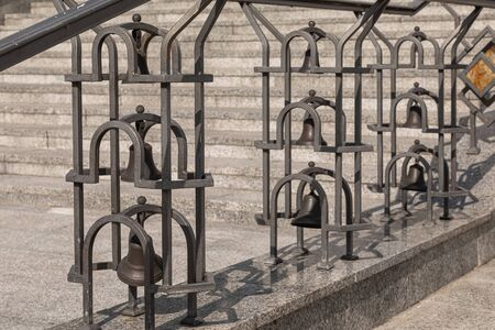 Close-up of wrought church bells in iron balustrade of outdoors stairs