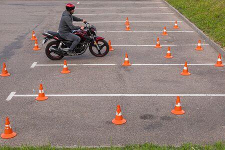 Minsk, Belarus - June, 2019.Man in helmet on motor-bicycle practising on parking space among traffic cones