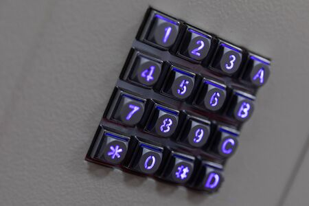 Black metal buttons with blue shiny lights numbers, including number sign hashtag and asterisk, A B C letters on gray abstract surface, diagonal view