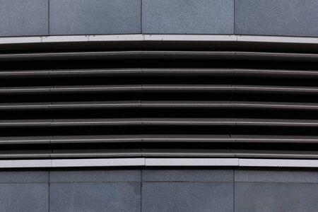 Horizontal ground ventilation grate on gray tiled floor