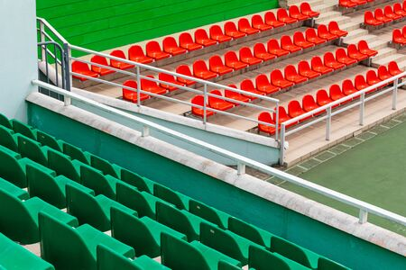 Diagonal view of competition venue with green and orange spectator seats. Stock Photo