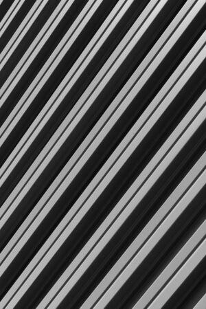 Vertical diagonal view of gray corrugated metal building facade 免版税图像