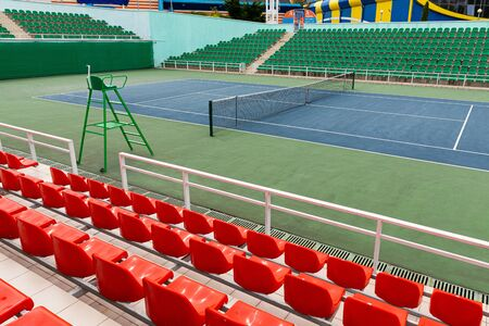 Sport stadium with several rows of spectator seating and tennis court at sport stadium or performance venue