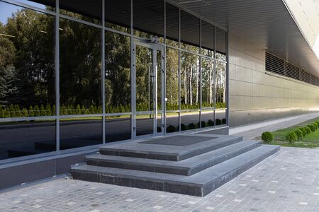 Glass doors reflecting bushes and trees in the opposite side and stone steps Stock fotó