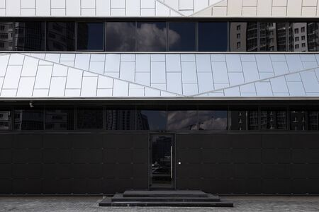 Modern and minimalistic black and white building with black smoked windows and glass door