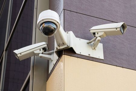 Ground view of three white surveillance cameras on office building with pale yellow and pale maroon tiled wall 免版税图像