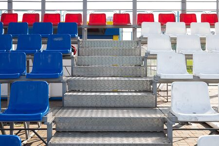 Front view of blue and red plactic seats on sport stadiums tribune with metal steps Stock fotó