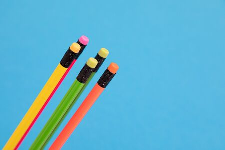 Five multicolored pencils are loosely and diagonally arranged on a pale-blue background cutout