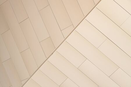 Angular view of light beige color tiled wall of refracted relief Stock Photo