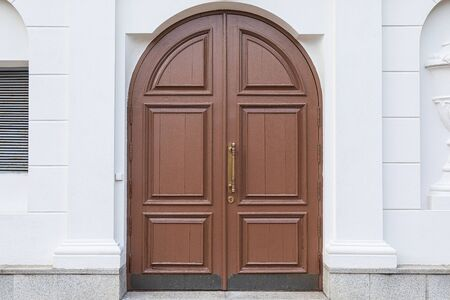 Arched brown wooden door in white wall