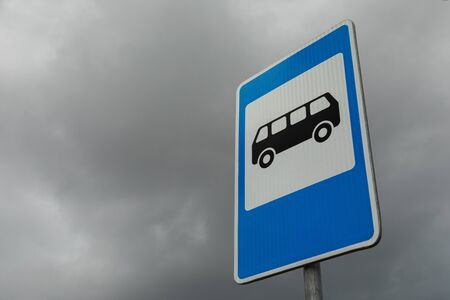 Rightangled blue and white roadsign of bus stop against dark cloudy sky