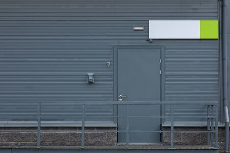 Emergency exit metal door with empty tablet above it Stock fotó