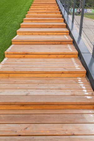 Wooden steps of light color going up near green lawn