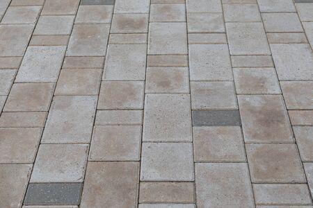 Nahaufnahme von grauen und beige Pflasterfliesen im Freien auf dem Boden