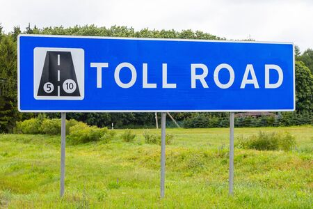 Roadsign Toll road against sky and field