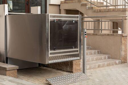 Treppenlift, Plattformlift, Behindertenlift in der Nähe moderner Apartmentanlage, Schrägansicht. Standard-Bild