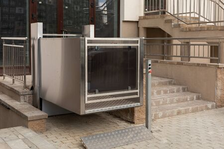 Cutting-edge metal city stair lift, platform lift, disabled persons lift outside apartment building, low angle view.