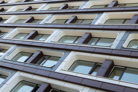 square streamline shaped windows on contemporary urban luxury designed accomodation facade. creative arcitecture, exterior Stock Photo