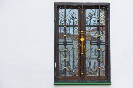 Wooden window of a church with wrough iron cross