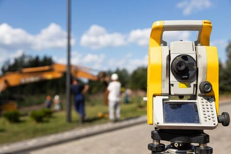 Close-up of yellow and orange tacheometer standing on street against work on construction site. Photo with depth of field Stock Photo