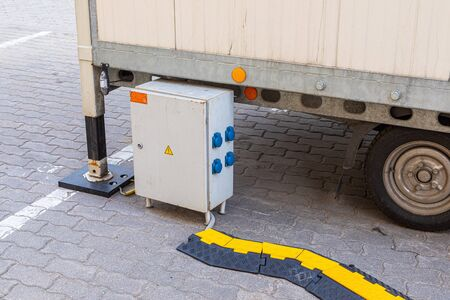 Electricity generator on street, plugged wires are covered with black and yellow warning street protection