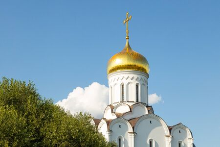 Top part of white Eastern church with gilt dome against clear blue sky and green tops of trees
