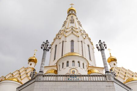 Bottom view of white Christian church with gilded domes