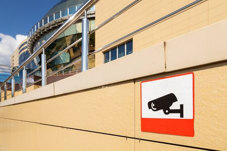 Close-up of sign informing about video monitoring area on beige building wall. Photo with depth of field