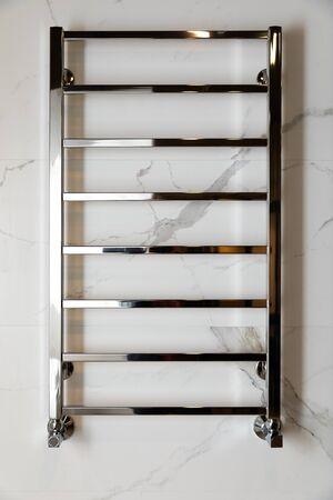 Shiny modern heated towel rail on tiled bathroom wall. Archivio Fotografico