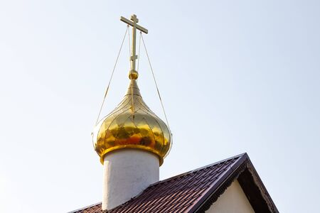 Close-up of gilded sunlit orthodox church dome with cross on top on red roof against white sunlit sky Stok Fotoğraf