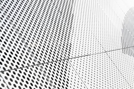 Diagonal view of metall grilles and round holes in metal surface, perforated panels close-up.