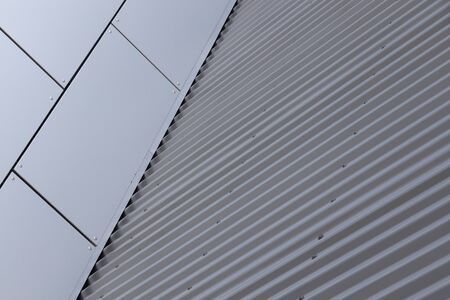 Angular view of corner of building - junction of grey smooth tiled wall and grey metal corrugated wall. Photo with depth of field