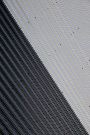 Close-up of junction of black and white corrugated surfaces with diagonal division. Industrial yin yang